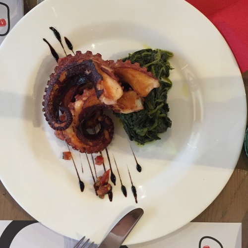 Perfectly roasted octopus on a bed of sauteed greens.